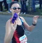 Tossing my gloves to my Mom around mile 4.  Who looks this happy during a half marathon?
