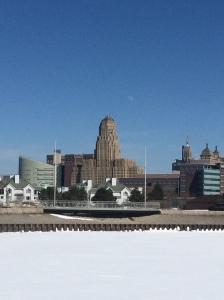 As seen on my (Sunday) run: City Hall over a frozen Erie Basin Marina.